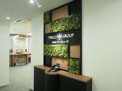 【オフィス受付の施工事例】アイキャッチ効果の高い、サインとフェイクグリーンの組み合わせ演出が素敵です。
